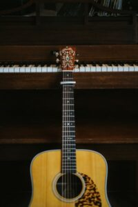 An acoustic guitar resting against a piano