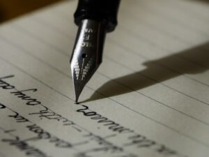 A person using a fountain pen to develop their language skills from digital learning