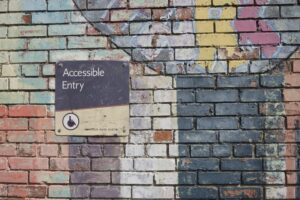 An accessible entry sign on a colourful wall