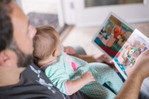 A father reading a colourful book to his baby