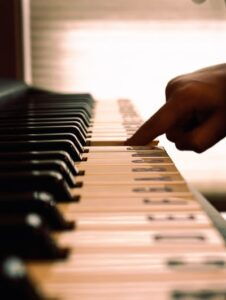 A person pressing a piano key with the notes written on the keys