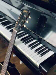 A black guitar resting on a Grand Piano