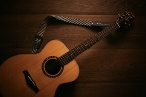 An acoustic guitar resting on a hardwood floor