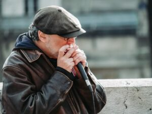 A man playing the harmonica in the public into a microphone