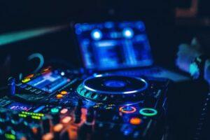 A DJ controller set lit up in fluorescent colours