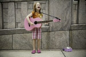 A young girl busking with a pink guitar on a street corner