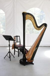 A large harp instrument in white marquee tent