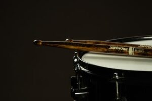 A close up view of a drum and two drumsticks