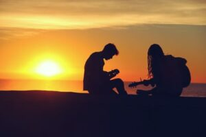 Two people playing the guitar silhouetted by a sunset in the background