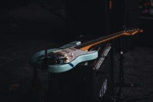 A Fender Stratocaster blue guitar resting on top of an amplifier