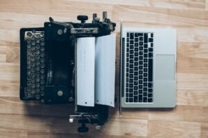 Digital learning methods vs traditional learning methods symbolised with a laptop and a typewriter