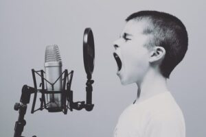 A young boy singing into a micriphone